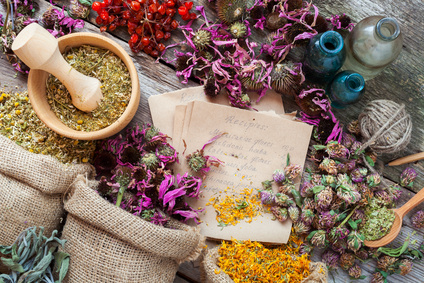 Healing herbs in hessian bags, wooden mortar, bottles with tinct